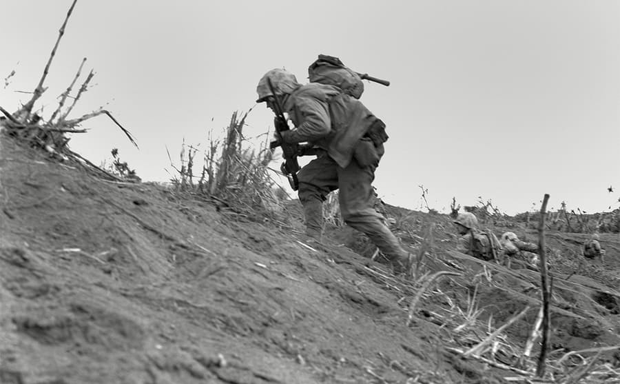Soldiers climbing on a mountain holding their weapons
