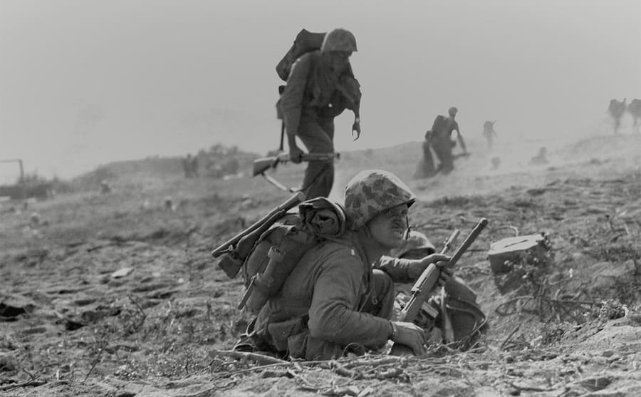 A soldier sitting in a foxhole behind him standing few more soldiers