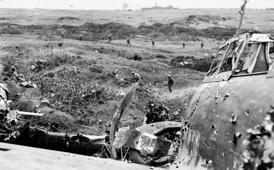 Soldiers walking by a wrecked military airplane