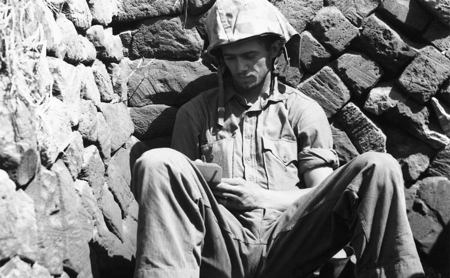 A soldier Marine sitting in a foxhole resting