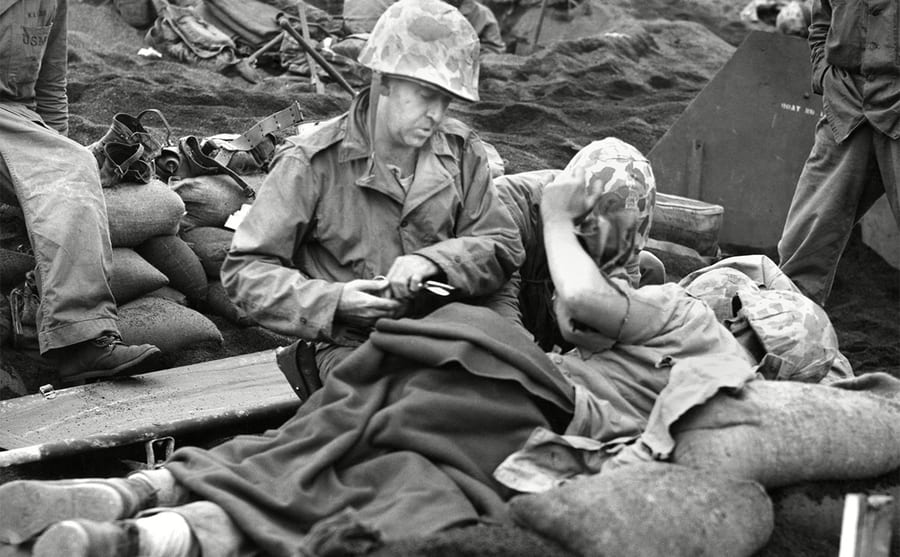 A navy doctor and corpsman treat a wounded Marine