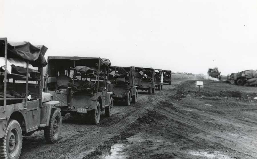 A convoy of Jeep ambulances driving through a valley
