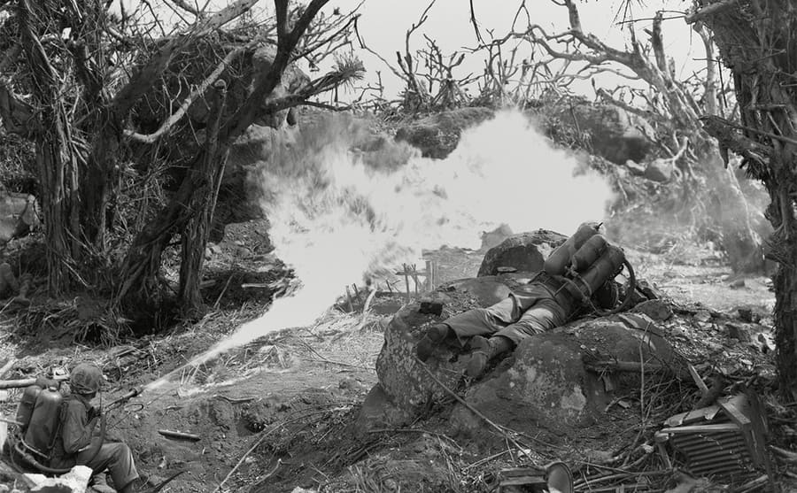 Two soldiers using a flame thrower and burning trees surrounding them
