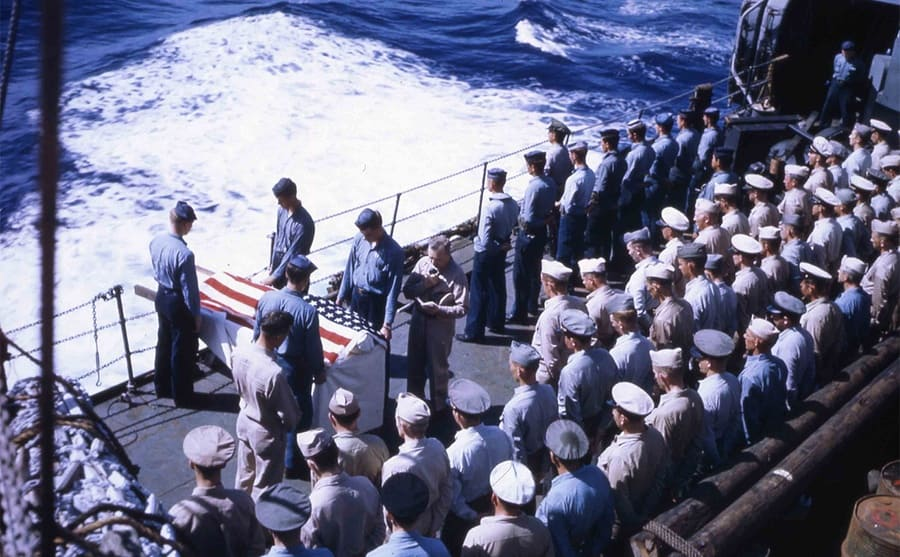 A group of Marine soldiers standing on the deck at a funeral ceremony