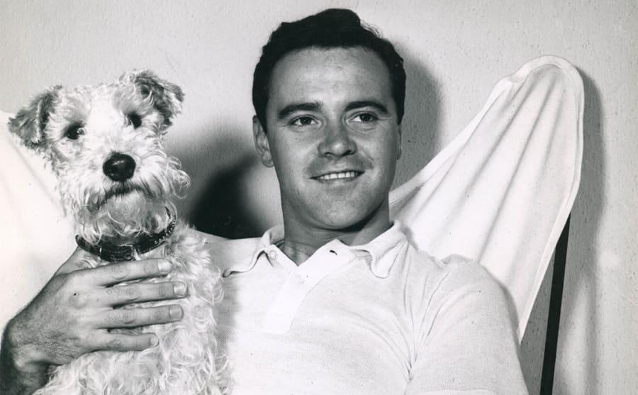 Jack Lemmon sitting holding a dog