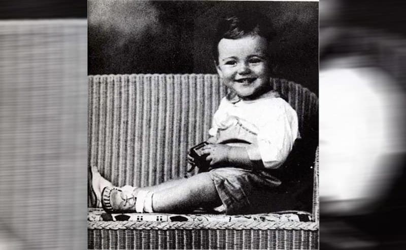 Jack Lemmon as babysitting on a chair smiling