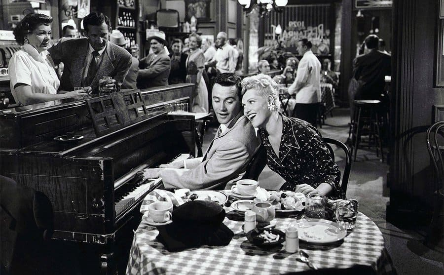 Jack Lemmon playing the piano next to Judy Holliday