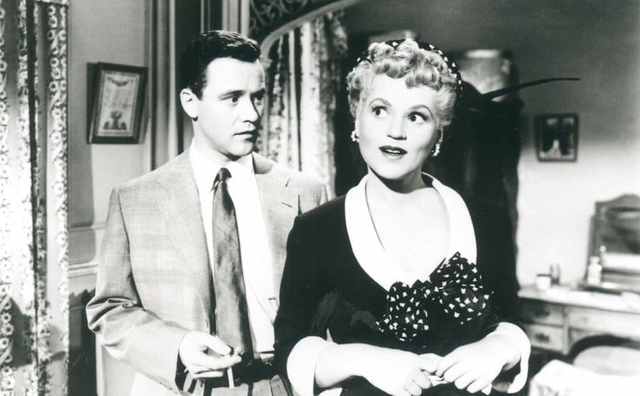Jack Lemmon standing behind Judy Holliday looking at her