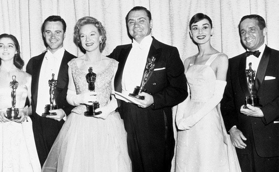 The winners of the Academy Awards standing in a row holding their Oscar statue