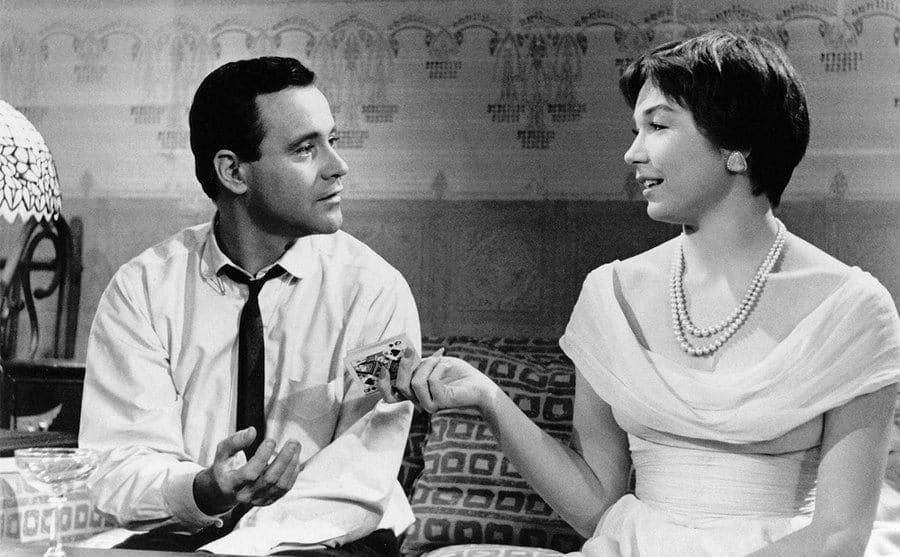 Jack Lemmon and Shirley MacLaine sitting next to each other while she passes him a card