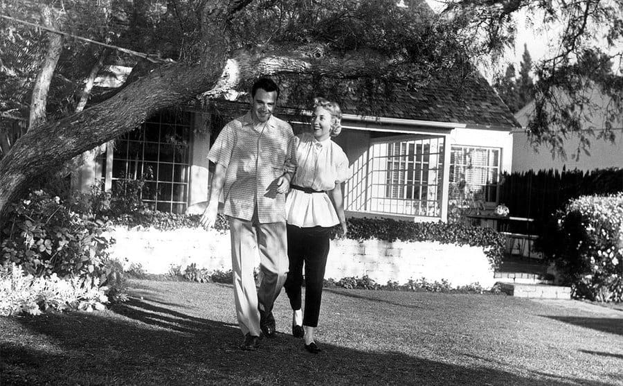 Jack Lemmon and Cynthia Stone walking on the front lawn of their home