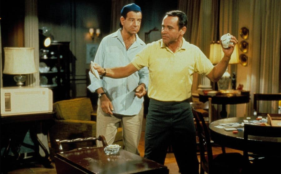 Walter Matthau and Jack Lemmon standing next to each other in a living room