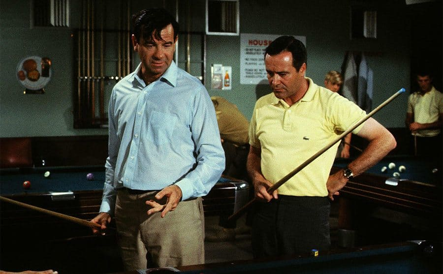 Walter Matthau and Susan Sarandon standing on either side of Jack Lemmon, who is sitting