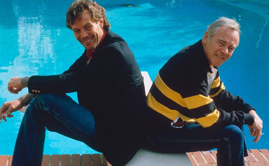Jack and Chris Lemmon sitting back to back in front of the pool at their home