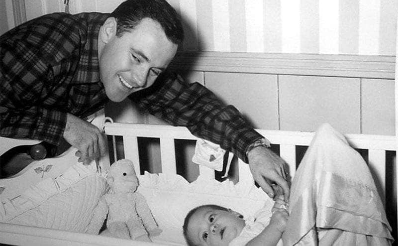 Jack Lemon is leaning towards his son's crib and smiling