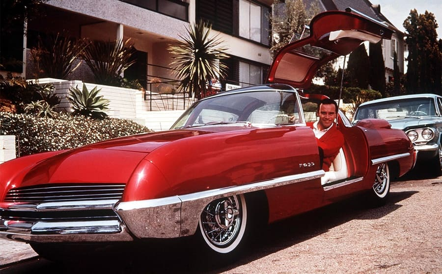 Jack Lemmon sitting in a red car