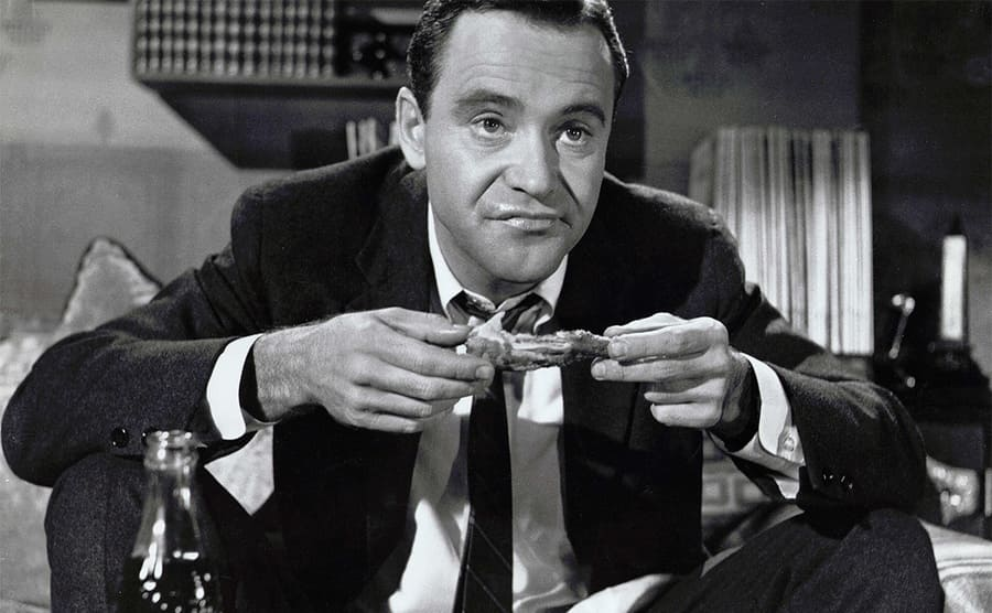 Jack Lemmon sitting and eating a chicken