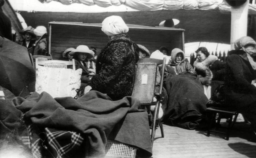 Survivors sitting on the deck with blankets and coats