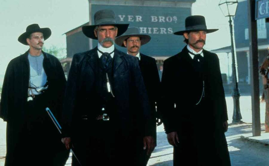 Val Kilmer, Sam Elliot, Bill Paxton, and Kurt Russell walking through the streets in the film Tombstone