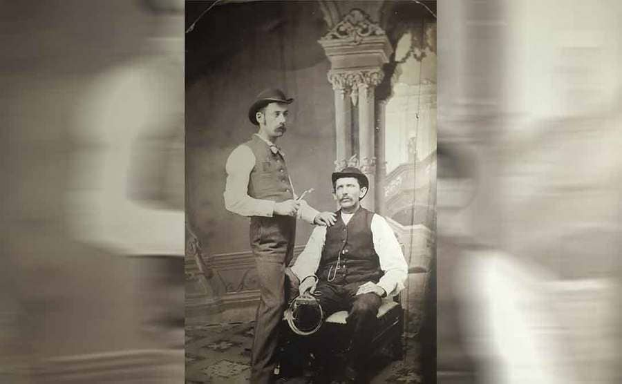 Doc Holliday holding dentistry tools with a man sitting in his chair