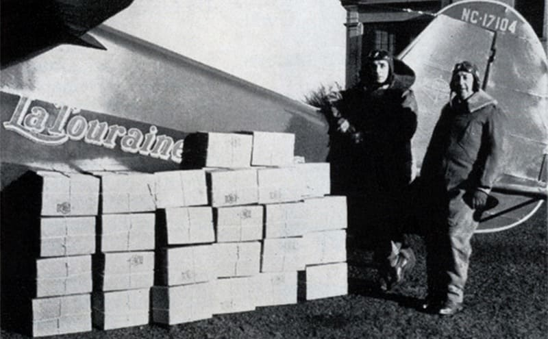 William and Bill Jr posing at the back of their aircraft with a stack of boxes