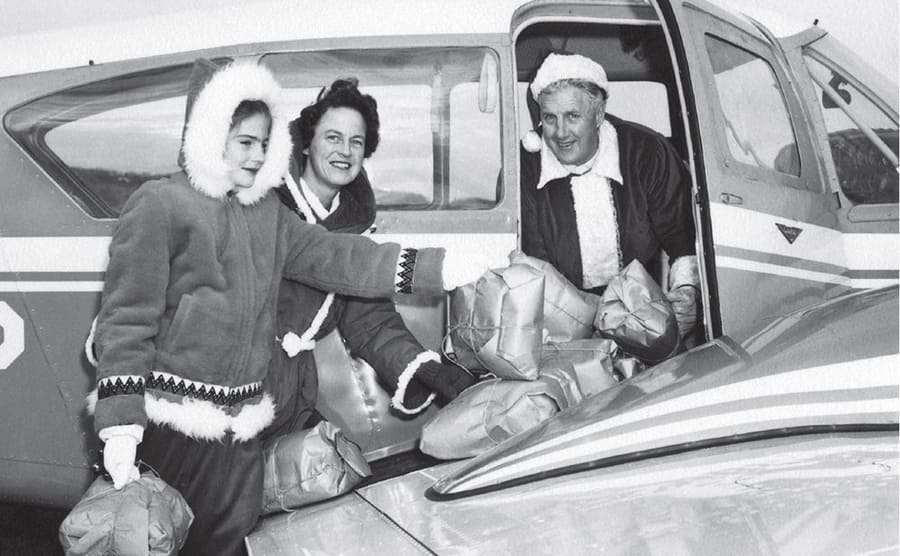 Edward Snow delivering packages to two women dressed for a cold winter
