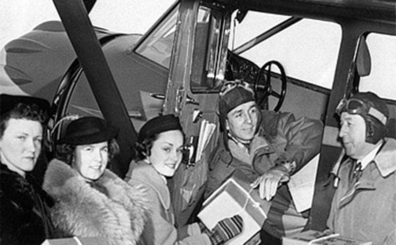 William Sr and Jr delivering packages to a group of women