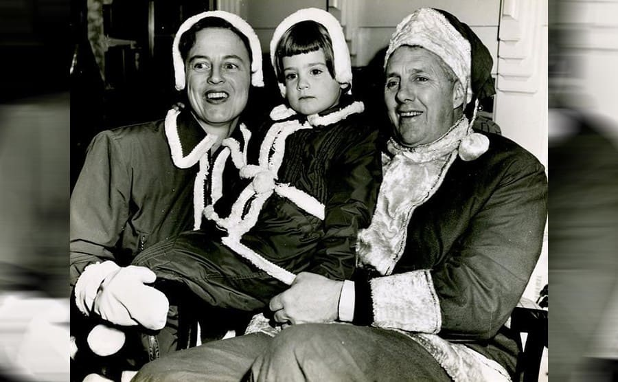Anna-Meryle, Dolly, and Edward Rowe Snow posing in Santa-like outfits in 1954