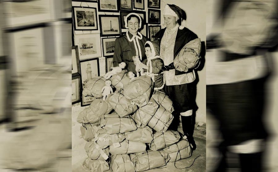 Edward Rowe Snow with his wife and daughter standing next to a large pile of packages and dolls