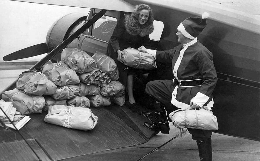 Edward Rowe and his wife loading packages into the airplane