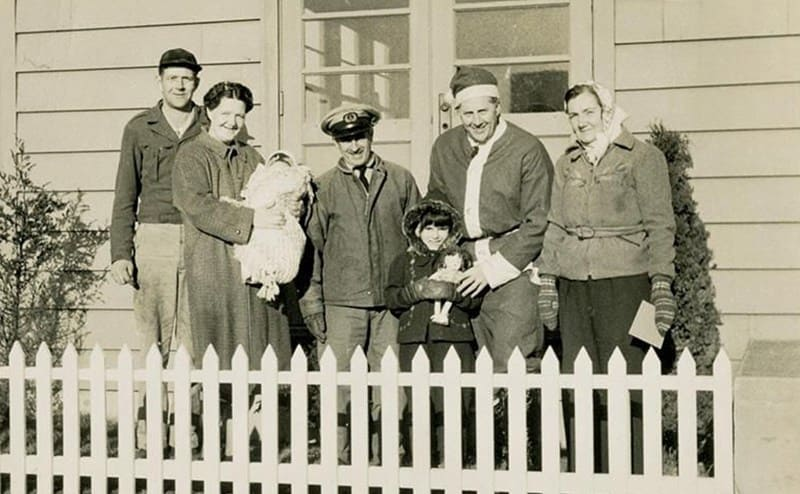 Snow as Flying Santa with Seamond and her family posing behind a white picket fence