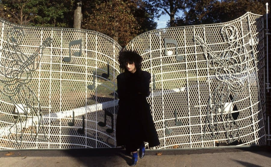 Boy George standing in front of the gate with musical notes