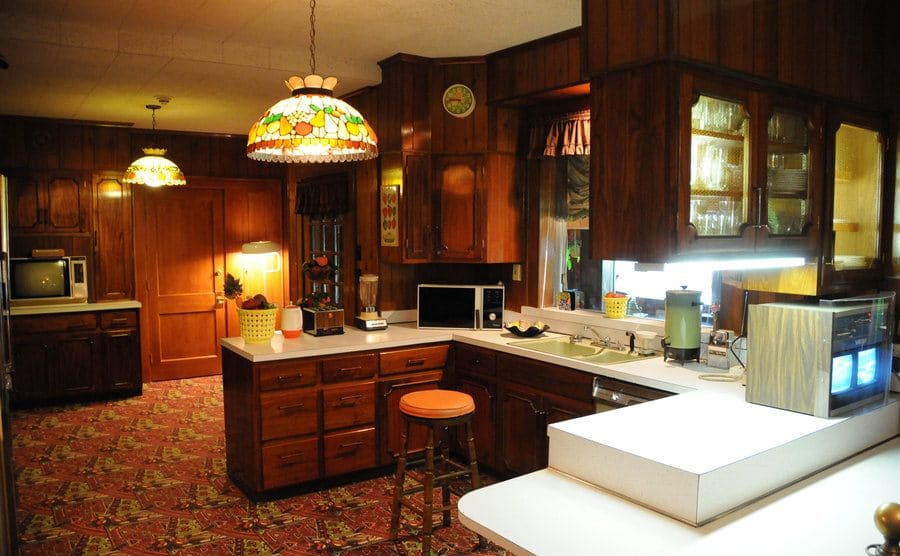 Elvis' carpeted kitchen with dark wooden cabinets and walls and white countertops