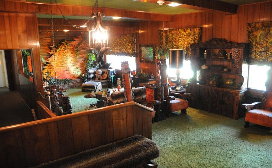 The Jungle Room with light green carpeting and dark leather chairs
