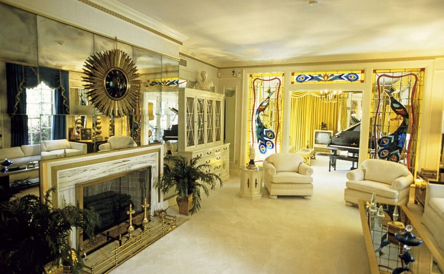 Elvis' living room with white carpets and chairs, blue curtains, and a mirrored wall surrounding the fireplace