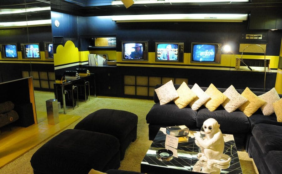 The TV room with three televisions, carpeting, black sofas, and a mirrored wall