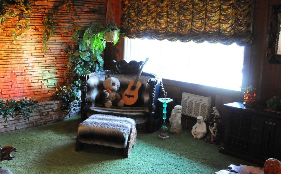 The Jungle room with moneky statues on the floor next to the window