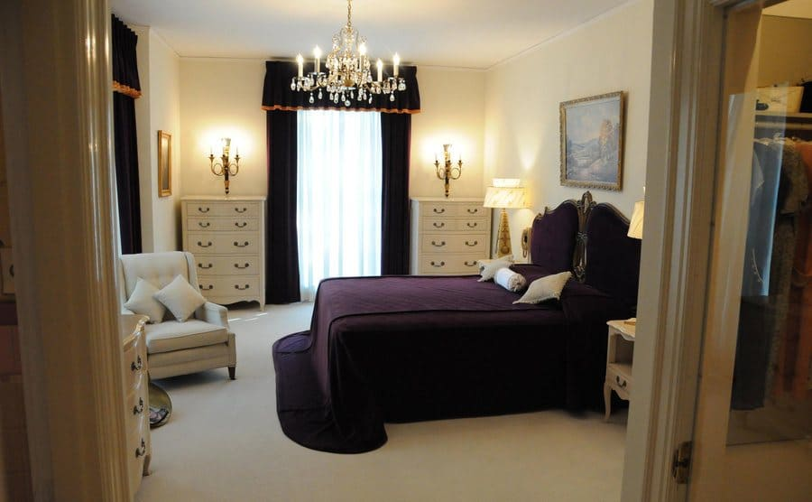 The master bedroom in white with dark purple drapes and bedding