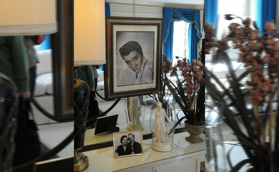 Elvis' dresser with a portrait of him hung up and a photograph of his parents standing up
