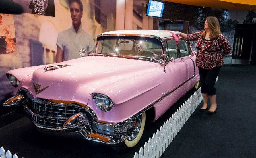 A woman dusting off Elvis' pink Cadillac, which is on display behind a short white fence