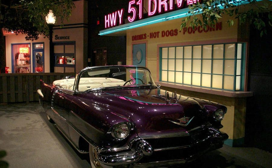 Elvis' purple car parked in front of a small diner