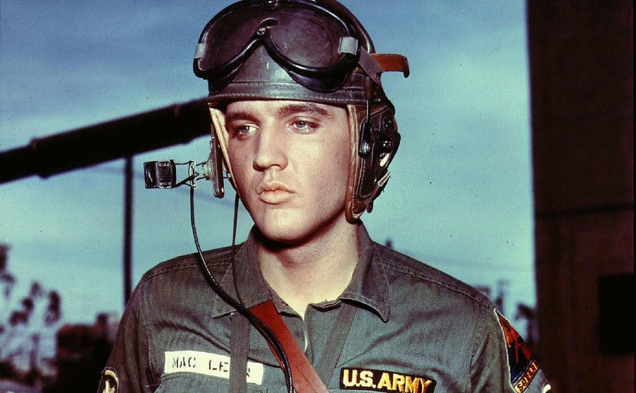 Elvis Presley in a uniform with his helmet on ready to fly in the film GI Blues