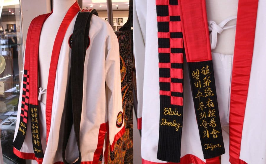 Elvis Presley's karate Gi with the black belt draped over it / A close-up photograph of the red and black belt with his name and letters embroidered on it