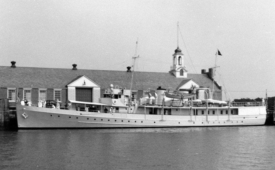 The USS Potomac docked in front of a ranch-style building
