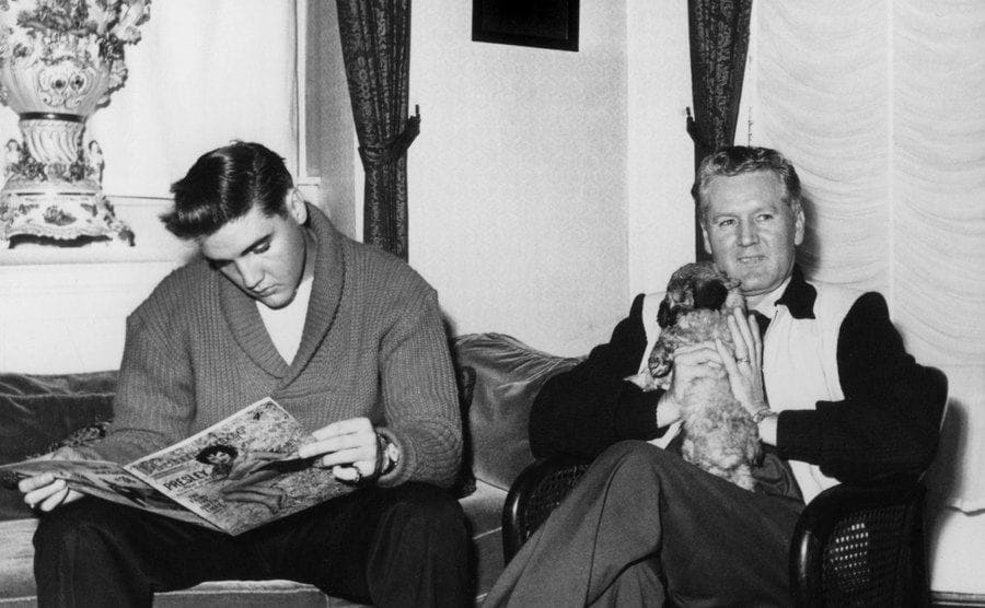 Elvis and Vernon Presley in his living room reading a magazine while his father is holding a small dog