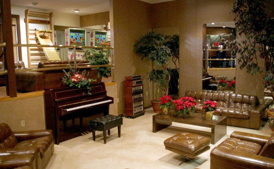 A beige themed room with brown couches, a piano, and mirrors on the walls