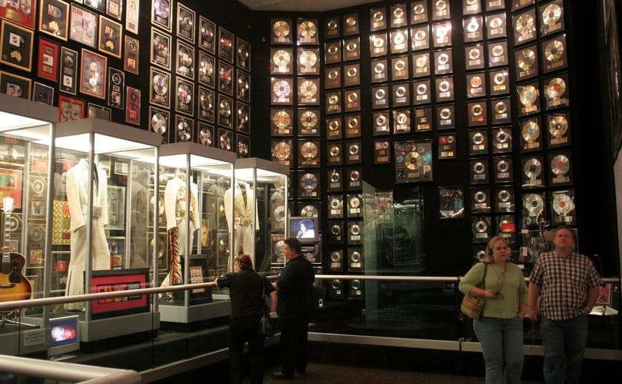 A room with records and photographs lining the walls and his jeweled suits on display in glass cases