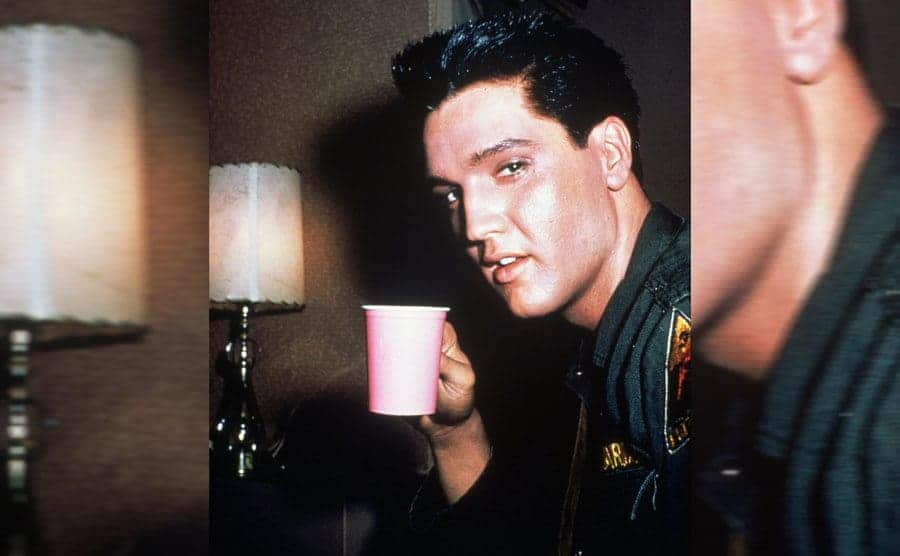 Elvis Presley holding a cup