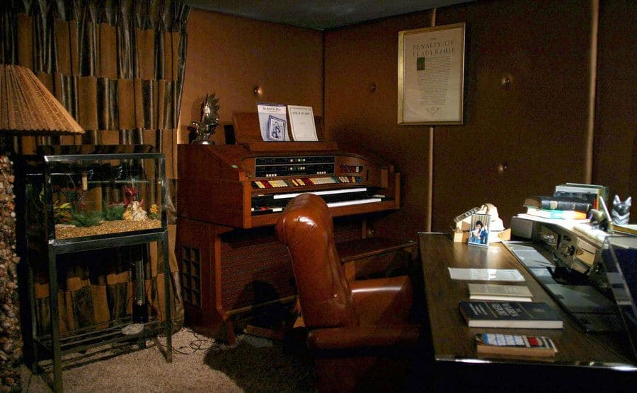 Elvis Presley's office room with a desk in the center and a piano and fish tank behind it