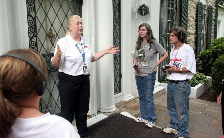 A guide greeting visitors on the front porch of Graceland